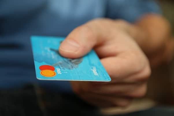 Client qui tend sa carte bancaire pour payer
